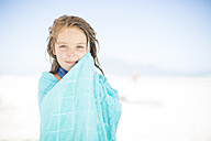 Smiling girl on beach wrapped in a towel - ZEF003369