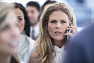 Annoyed businesswoman on cell phone in busy city - ZEF003241
