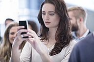 Annoyed woman looking on cell phone in busy city - ZEF003434