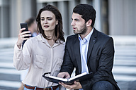 Businessman and woman with diary and cell phone in the city - ZEF003256