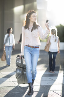 Woman pulling suitcase and looking at cell phone in the city - ZEF003267