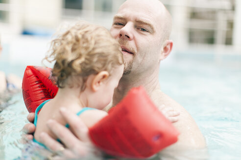 Father carrying little daughter in swimming pool - NNF000287
