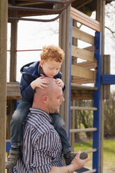 Father carrying son on playground - NNF000307