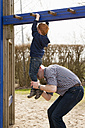 Father helping son on playground climbing on jungle gym - NNF000310