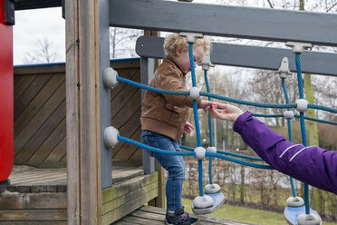 Mother helping little daughter walking on playground equipment - NNF000328