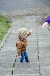 Little girl walking up stairs waiting for her mother - NNF000329