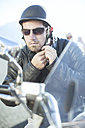 Man on motorcycle tying helmet strap - ZEF003620
