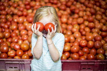 Little girl in front of tomato stall covering eyes with tomatoes - ZEF004187