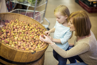 Mother and daughter at supermarket shopping for lychees - ZEF004190