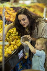 Mother and daughter at supermarket shopping for peaches - ZEF004192