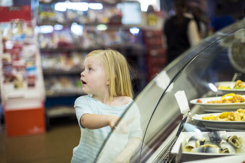 Little girl pointing at food at display - ZEF004172