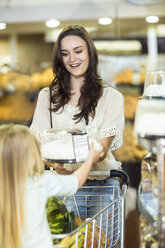 Mother and daughter with shopping trolley buying cake - ZEF004174