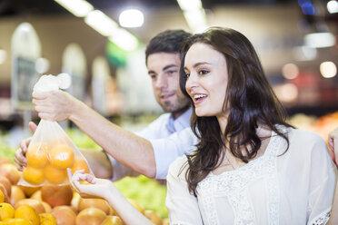 Shop assistant helping client choosing oranges - ZEF004211