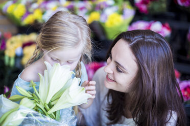 Mother and daughter smelling flower in shop - ZEF004215
