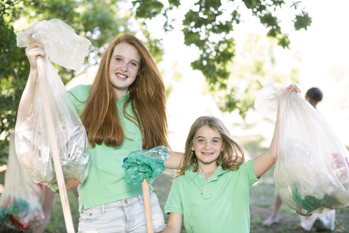 Portrait of two smiling girls showing picked up garbage - ZEF004369