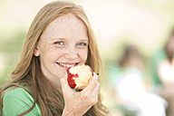 Portrait of smiling girl with red hair eating an apple - ZEF004384