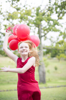 Portrait of running girl with red balloons wearing red dress - ZEF004391