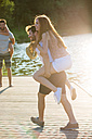 Happy young man carrying girlfriend piggyback on jetty at a lake - WESTF020714