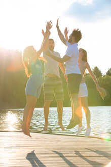Four friends high fiving at a lake in backlight - WESTF020717