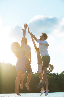 Four friends high fiving at a lake in backlight - WESTF020720