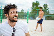 Smiling young man on beach volleyball field - WESTF020722
