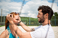 Young couple on beach volleyball field - WESTF020729