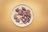 Chocolates on plate and yellow background - LVF002586
