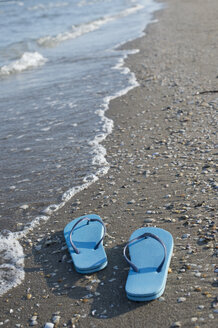 Italy, Adriatic Sea, blue flip-flops at seafront - CRF002632