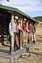 USA, Wyoming, cowgirl and three cowboys standing under a porch - RUEF001357
