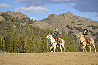 USA, Wyoming, two young cowboys riding - RUEF001373