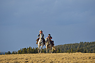 USA, Wyoming, two young cowboys riding - RUEF001384