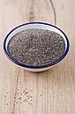 Enamel bowl of chia seeds on wood - ODF001007