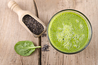 Glass of spinach smoothie, shovel of chia seeds and spinach leaf on wood - ODF001012