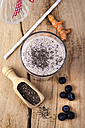 Glass of blueberry smoothie, wooden shovel of chia seeds, curcuma and blueberries on wood - ODF001006