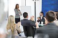 Businesswoman in boardroom leading a meeting with flip chart - ZEF003122