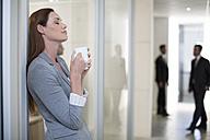 Businesswoman having a coffee break on office floor - ZEF003126