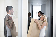 Businesswoman carrying big box through office - ZEF003160