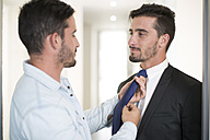 Casually dressed man adjusting tie of twin brother in office - ZEF003140