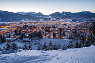Germany, Bavaria, view to snow-covered lighted Oberstdorf in front of the Allgaeu Alps - WGF000562