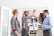 Happy businesspeople high fiving in office - WESTF020589