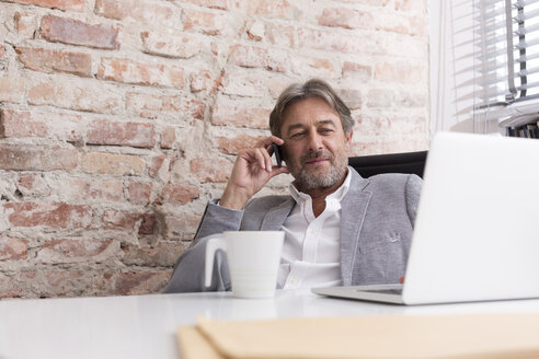 Businessman with cell phone and laptop at desk - WESTF020631