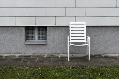 White plastic chair standing in front of a facade - EJW000623