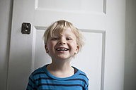 Portrait of laughing little boy in front of white door - RB002236