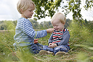 Two little brothers sitting on a meadow - RB002254