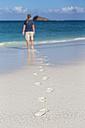 Ecuador, Galapagos Islands, Espanola, tourist walking on beach - FOF007304