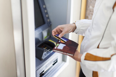 Woman at cash machine - NNF000193