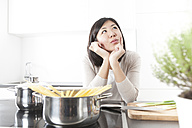 Portrait of pensive young woman cooking spaghetti - FLF000797