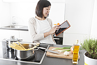 Smiling young woman using digital tablet while cooking - FLF000798