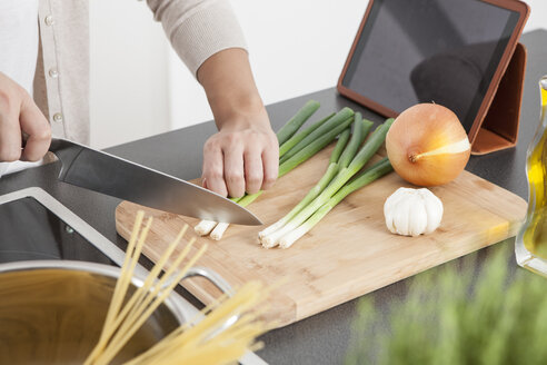Woman cutting spring onions in the kitchen - FLF000799
