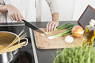 Young woman cutting spring onions on wooden board - FLF000800